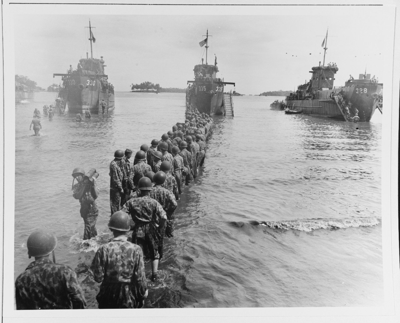 Troops unloading ammunition from LCI-330, 335, and 328 during landing operations at Rendova Island, 30 June 1943.